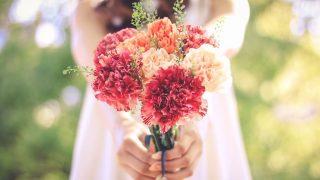 花束でお祝い。カーネーションの花束を持っている女性。
