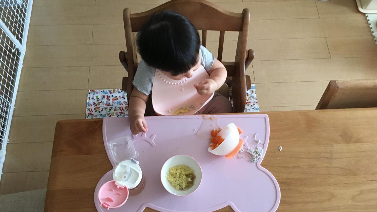 子どもが食事エプロンをつけて食事をしている様子。
